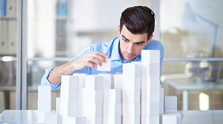 Businessman building towers with blocks