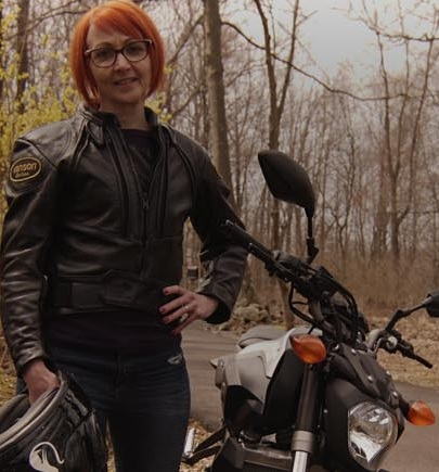 Lisa Woodley pic, standing near bike with helmet in her hand
