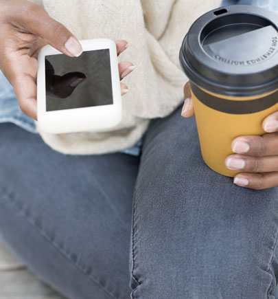 Woman using smartphone in lap with coffee