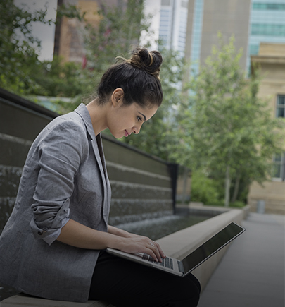 Business woman working on laptop outdoors