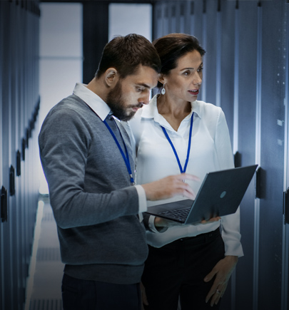 Businessman and woman on laptop in data centre